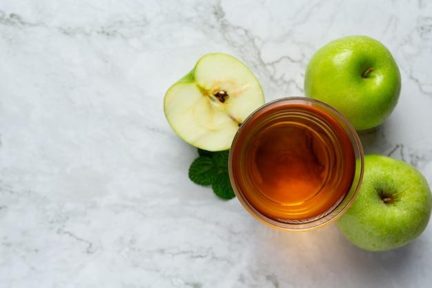 Verre de thé sain de pomme verte mis à côté de pommes vertes fraîches