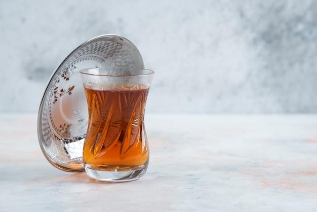 Verre de thé sur une surface blanche