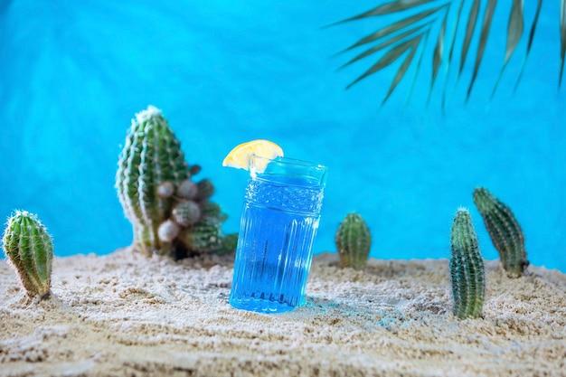 Un verre de thé thaïlandais bleu sur le sable avec des cactus