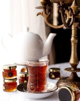 Verre de thé et théière sur la table