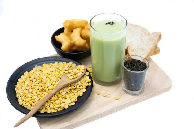 Verre de thé vert et de lait de soja. lait de soja matcha en verre et sur table en bois blanc. boisson végétarienne saine.
