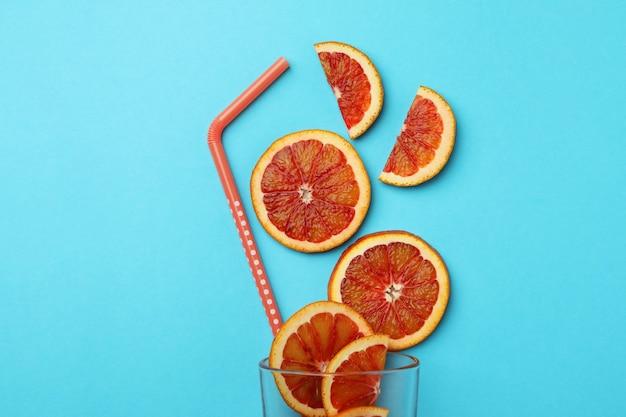 Verre avec des tranches d'orange rouge et de la paille sur fond bleu isolé