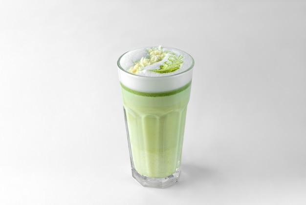 Verre transparent avec café au lait vert, lait moussé, sirop, crème fouettée et garniture isolé sur une surface blanche et grise