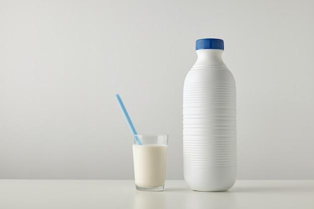 Verre transparent avec du lait frais et de la paille bleue à l'intérieur près d'une bouteille vide en plastique à rayures avec bouchon bleu