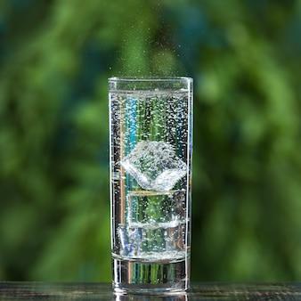Un verre transparent avec des glaçons et de l'eau pétillante