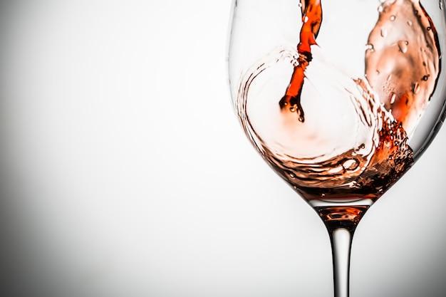 Verre transparent sur une tige mince sur un fond blanc avec du vin