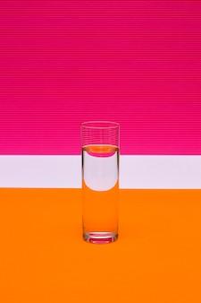 Verre avec un verre de liquide sur un fond coloré