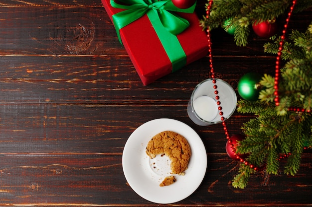 Verre vide de biscuits de lait et de miettes et un cadeau sous le sapin de noël. le de l'arrivée du père noël.