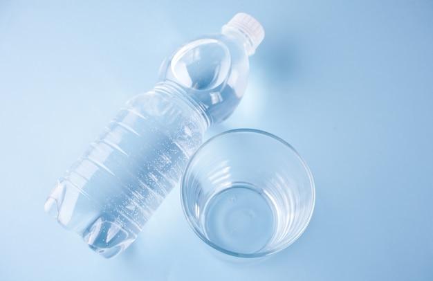 Verre vide et bouteille avec de l'eau sur un fond bleu