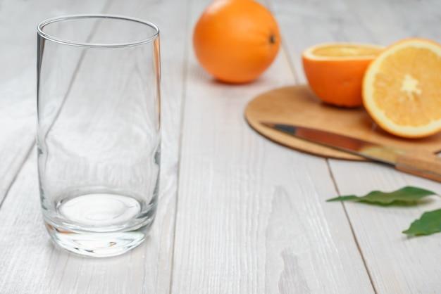 Verre vide et oranges en arrière-plan