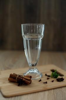 Verre vide sur une plate-forme en bois avec les ingrédients pour préparer une boisson vitaminée chaude