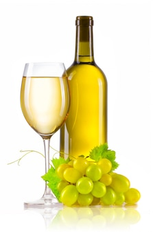 Verre de vin blanc avec une bouteille et des raisins mûrs isolés