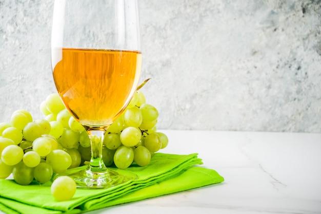 Verre à vin blanc avec une branche de raisin