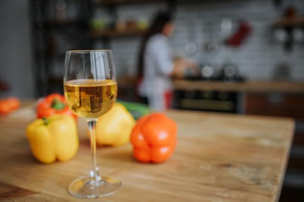 Verre de vin blanc sur un bureau avec des poivrons jaunes et orange