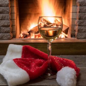 Verre à vin blanc et chapeau de père noël de noël contre la cheminée