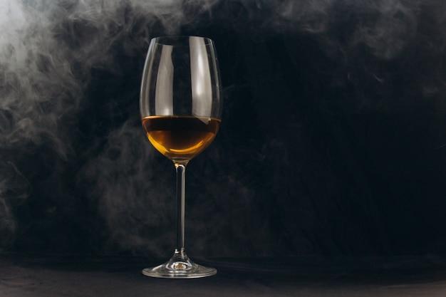 Un verre de vin blanc sur fond noir. la fumée du narguilé enveloppe le verre.