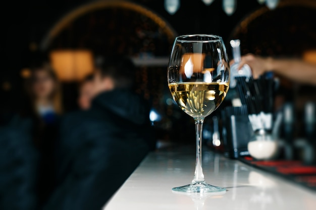 Un verre de vin blanc en gros plan sur un comptoir de bar blanc