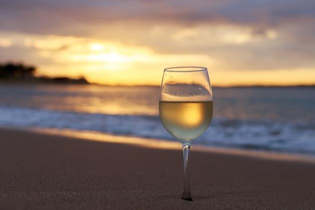 Un verre de vin blanc sur la plage au coucher du soleil.