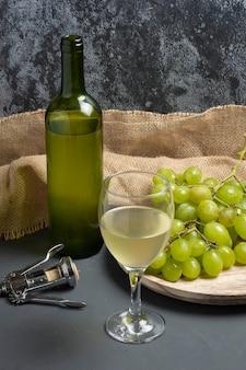 Verre à vin blanc avec des raisins dans une atmosphère de cave