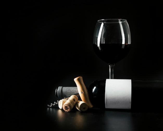 Verre à vin et bouteille près de tire-bouchon et de bouchons