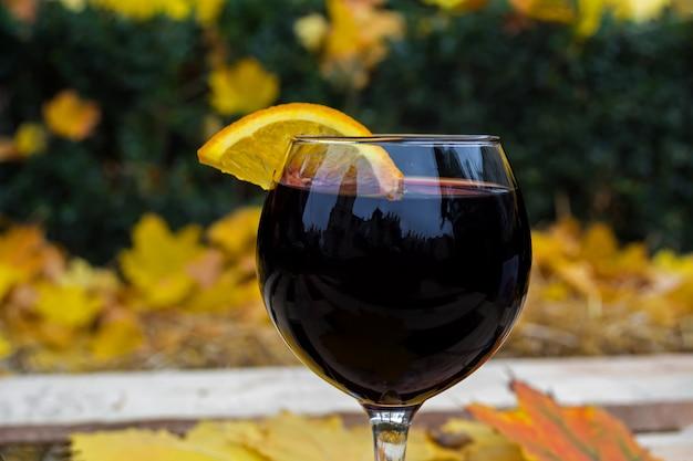 Un verre de vin chaud dans un automne froid, sur fond de feuilles jaunes et rouges