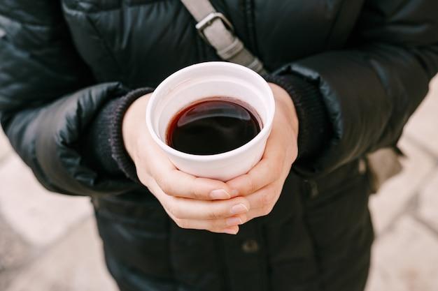 Verre de vin chaud dans les mains des femmes au marché de noël en allemagne
