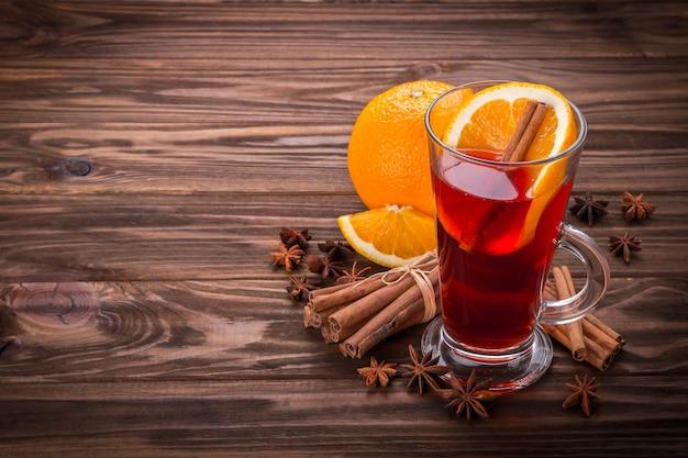 Verre à vin chaud, épices et fruits sur fond en bois