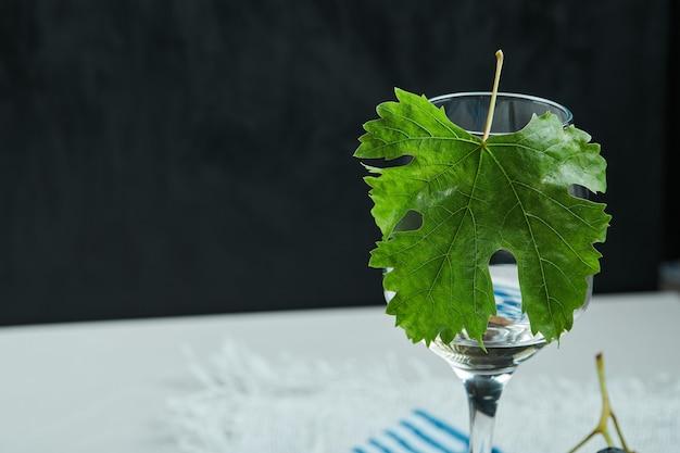 Un verre de vin avec feuille sur table blanche