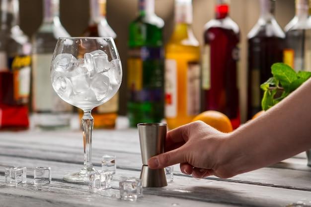 Verre à vin avec glace et jigger. main masculine avec bar jigger. outil de barman. choisissez les ingrédients de votre cocktail.