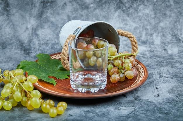 Un verre de vin avec une grappe de raisin vert.
