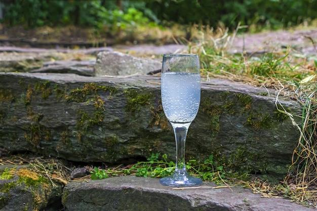 Verre à vin avec de la limonade sur rocher, des pierres parmi la mousse.