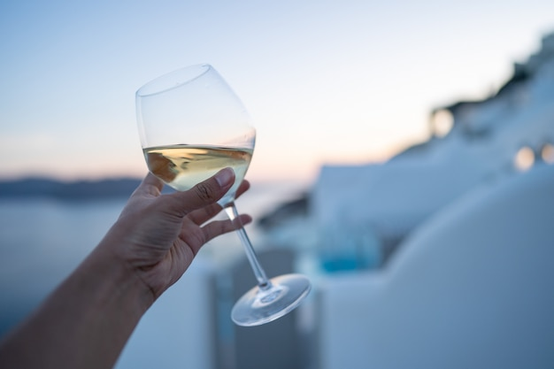 Un verre de vin à la main.