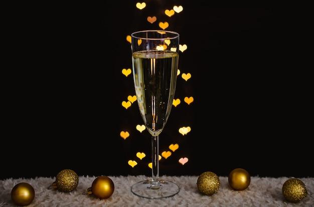 Un verre de vin mousseux avec des ornements de noël dorés avec des lumières bokeh en forme d'amour.