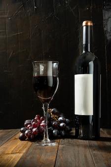Verre à vin plein à côté d'une bouteille de vin rouge sur une table en bois rustique et fond sombre. grappe de raisin derrière.