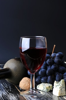 Verre de vin raisins bouteille d'alcool fromage fond en bois usé style vintage rétro