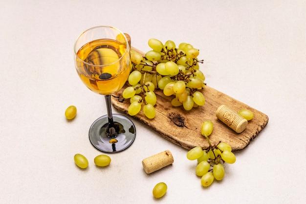 Verre à vin, raisins frais et bouchons sur planche à découper en bois