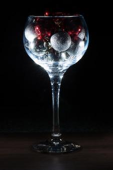 Verre à vin rempli de boules de noël. sur un fond noir