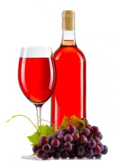 Verre de vin rosé avec bouteille et raisins mûrs isolés