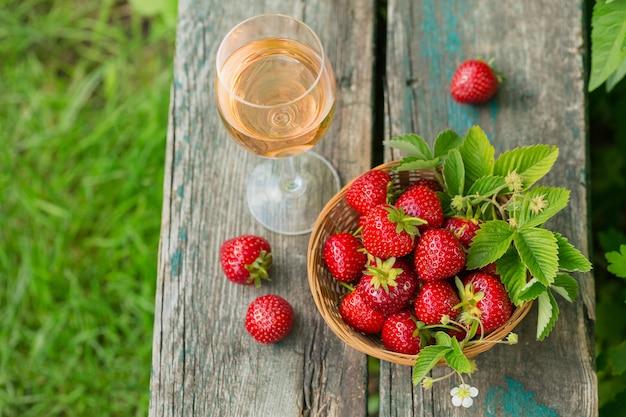 Un verre de vin rosé servi avec des fraises fraîches sur bois