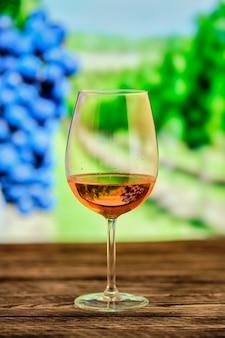Verre de vin rosé avec vignoble flou
