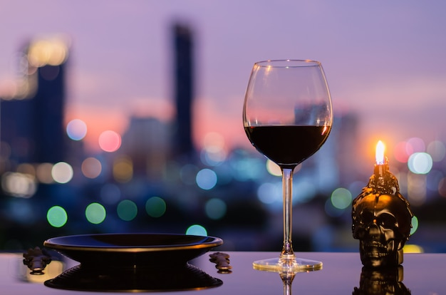 Un verre de vin rouge avec une assiette noire, un couteau, une fourchette et une bougie crâne sur fond clair de bokeh de la ville. concept de salle à manger d'halloween.
