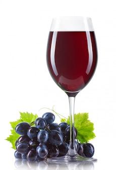 Verre de vin rouge avec une bouteille et des raisins mûrs isolés