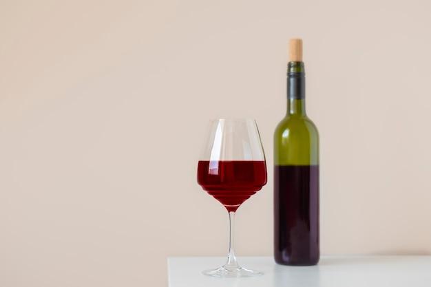 Verre à vin rouge avec une bouteille de vin sombre sur un intérieur simple de table blanche avec espace de copie