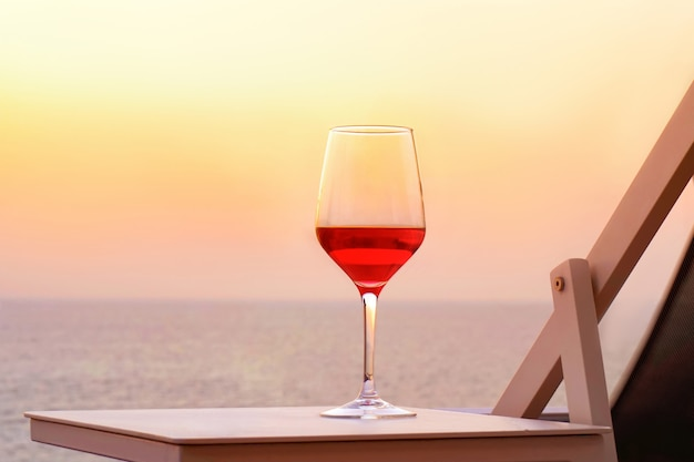 Un verre de vin rouge sur fond de mer au coucher du soleil. concept de date romantique