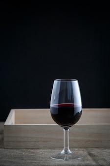 Un verre de vin rouge sur fond noir, support en tissu en bas