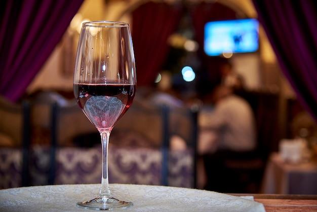 Verre à vin rouge sur un fond de restaurant flou
