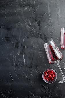 Verre à vin rouge et graines de grenade, sur fond texturé noir avec un immense espace pour le texte, vue de dessus.