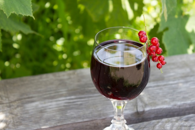 Verre de vin rouge avec des groseilles rouges sur la nature, le concept de vinification