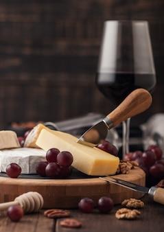 Verre de vin rouge avec sélection de divers fromages sur le plateau