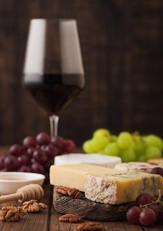 Verre de vin rouge avec sélection de divers fromages